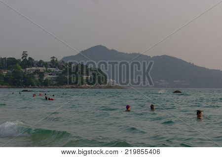 PANWA BAY AND BEACH, PHUKET ISLAND, THAILAND - MARCH 29, 2016: a Beautiful landscape seaview with swiming people and boats at beach of Laem Panwa Cape famous attractions in Phuket island, Thailand