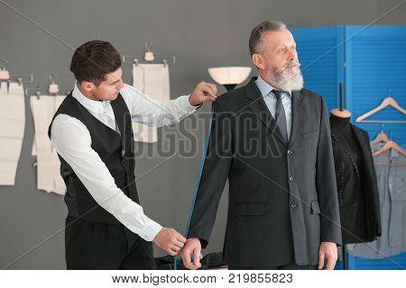 Tailor taking client's measurements in atelier poster