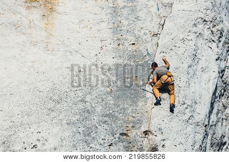 Poland Podlesice - March 04 2017: Side view of adult male rock climber on vertical flat wall with poor relief. Gora Zborow is a very popular destination among climbers