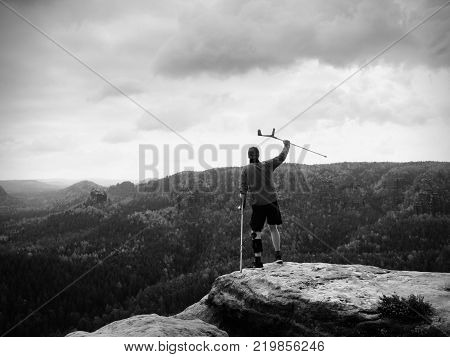 Man with forearm crutch. Hiker finaly achieved mountain peak. Tourist with broken leg in immobilizer hold medicine poles.