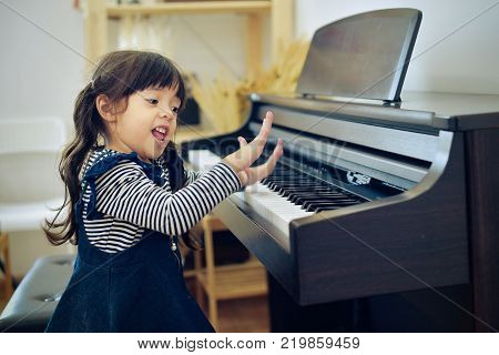 Little girl playing the piano at home,family and relaxing concept.