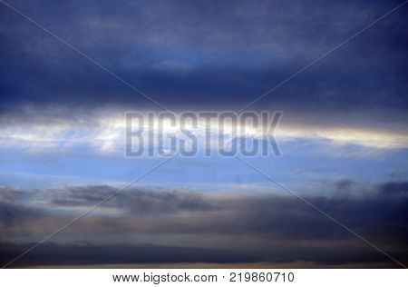 Strange and unusual cloud spiral pink orange gold and blue sunset in the sky