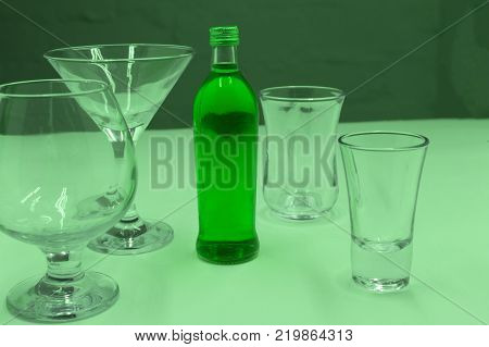 Absinthe cold water standing in glass bottles on the table. Next a plate of caramel and glasses for drinks poster