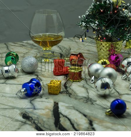 Fir-tree branch glass and New Year's toy. Glass with drink and a Christmas ball on a black background. New Year's ball and glass. Glass with alcohol and a Christmas ball