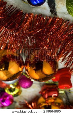 Christmas decoration with many glitter bauble balls shinny baubles and pine cones on the artificial pine tree .