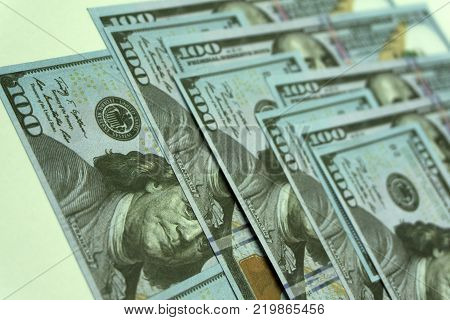 American dollars. A stack of hundred dollar bills. Close up of new hundred dollar bill on the blue background