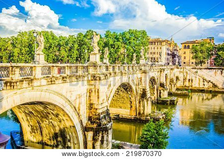 Saint Angel bridge with mirror reflection in Tiber river in Rome, Italy.