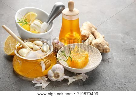 Composition with honey and garlic as natural cold remedies on grey textured background