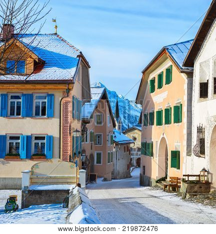 Narrow street with  typical houses  in the older part of Guarda at sunny winter morning,  Inn District,  Swiss canton of Graubunden, Switzerland.