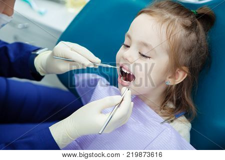 Child lies with open mouth and napkin on chest in comfortable dentist chair and doctor in sterile rubber gloves does checkup with special metal medical instruments.