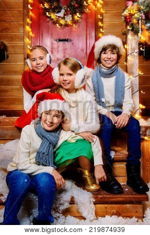 Four cheerful children in winter clothes and accessories  are posing near the house decorated for Christmas. Time for miracles. Merry Christmas and Happy New Year.