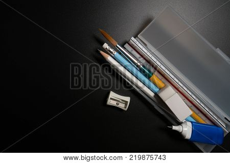 Basic White Plastic Pencil Box With Pencil, Pen, Eraser, Sharpener And Paintbrush On Black Backgroun