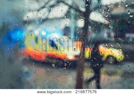 Emergency medical service response in the city. Ambulance cars on the rush street during rain. View through a car window and selective focus on the raindrop. Prague Czech Republic.