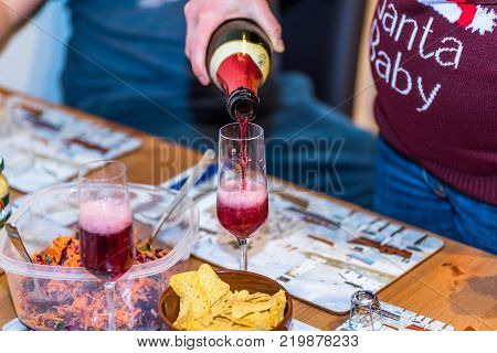 Pregnant female in christmas pullover holding bottle and pouring red non alcoholic wine into champagne glass on table.