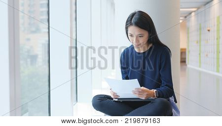 Student studying on paper note inside university campus, reading and revise on note, prepare for exam