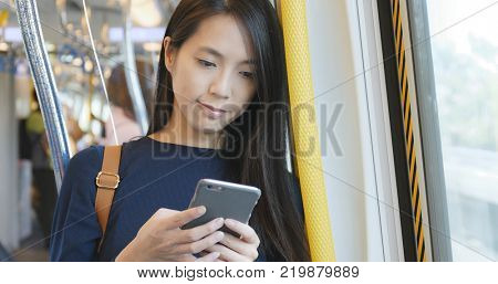 Woman working on mobile phone, mobile office concept, using cellphone for replying customer message on train compartment