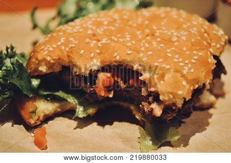 hamburger in a restaurant. Hamburger, beef and vegetables to bite one. junk food as concept.