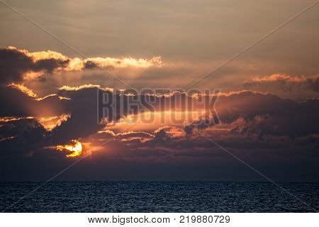 Beautiful sunrise over an ocean horizon. Dawn at sea. Orange anticrepuscular rays as sun is emerging from behind autumnal clouds.