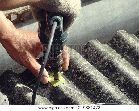 worker fixing dirty old roof with electric drill screwdriver