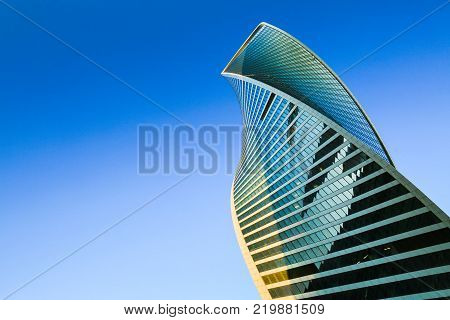 Moscow, Russia - September 10, 2017: Evolution tower. Moscow International Business Center. Skyscraper exterior. Modern office building, glass facade in blue sky. Urban view, looking up city, skyline.