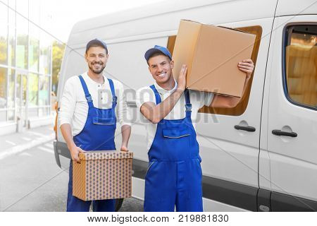 Delivery men with moving boxes near car