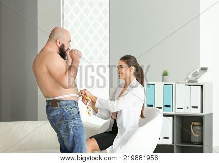 Young female doctor measuring waist of overweight man with centimeter in clinic
