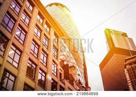 LONDON, UNITED KINGDOM - March 19, 2017: City of London. Modern and old architecture. The Gherkin building tower over the old buildings in the financial district of London. the sun at sunset is reflected on the glass of the skyscraper