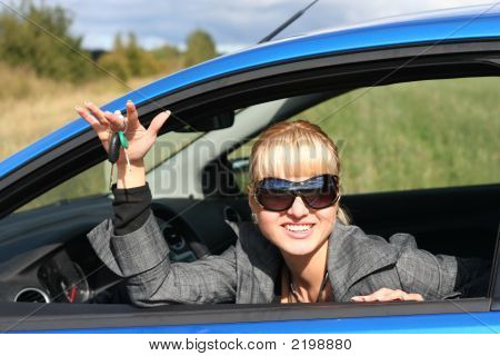 Young Blond Woman In A Blue Car With Key From It