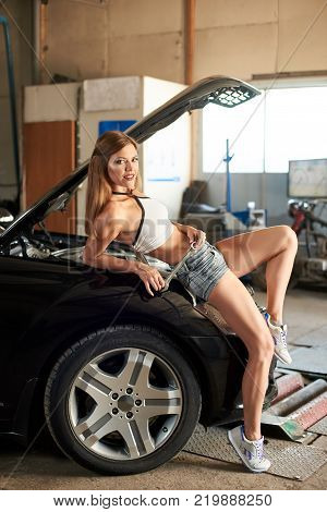 Black Car With An Open Hood And An Attractive Girl Leaned Against Him In The Garage. The Girl Is Ope