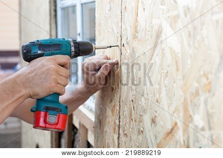Construction worker use screwdriver to attach Wood Particle Board (fiberboard) to the wall