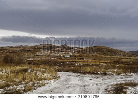 Dramatic dark winter steppe. Thaw. Ice road. City outskirts of the city of Ust-Kamenogorsk Kazakhstan