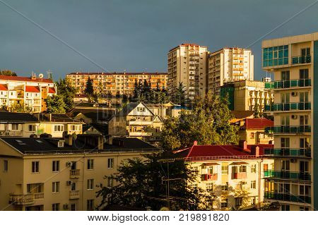 View of apartment buildings on the mountain in the in light of the setting sun on the background of thundercloud, Sochi, Russia
