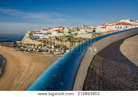 General view of Ericeira beach and houses under warm sunlight