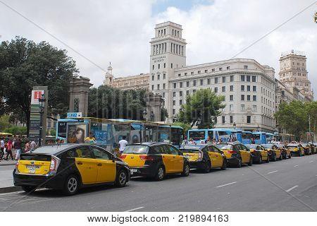 BARCELONA, SPAIN -August 2014: Big Taxi cars line near Plaza de Cataluña. Black a yellow taxi cars are waiting passengers near Plaza de Cataluña Barcelona Catalonia Spain.