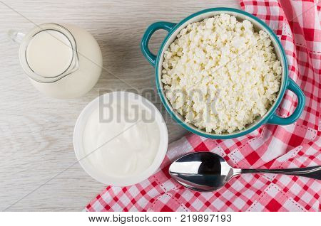 Cottage cheese in bowl jug of milk bowl with sour cream spoon and napkin on wooden table. Top view