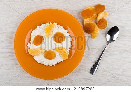 Cottage cheese with sour cream tangetines deied apricots in plate and spoon on wooden table. Top view