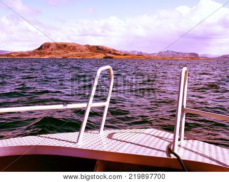 Midday boating in blue sea. Close view from boat bow metal deck. Metal handrail on the edge of the deck