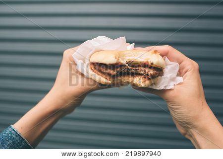 Eating hamburger. Delicious hamburger in the hands. Fastfood meal.