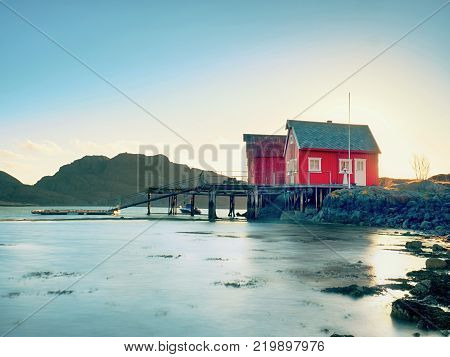 Norwegian coast landscape with a typical red house. Wooden red house on the seaside first warm spring day.