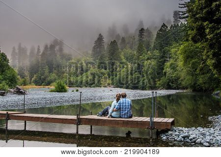 Couple Sits on Footbridge Over Calm Mountain River on Foggy Morning