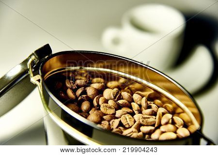 An open can with coffee beans on the background of a cup and a saucer