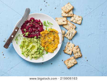 Variations of hummus and crackers. Pumpkin turmeric avocado beetroot hummus with olive oil sesame seeds and micro greens on a blue background top view