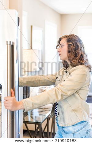 One young hungry woman opening modern stainless steel chrome kitchen refrigerator, fridge looking inside for food