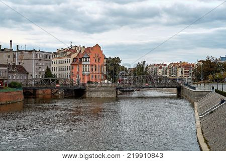 View from Tumski bridge to the bridge Mlynski with small touristic boats on Odra River and a tram on the bridge. Wroclaw, Poland
