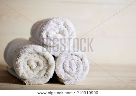 Towels on a wooden surface. Roll up towels on the table. Care cleanliness health. Spa treatments.