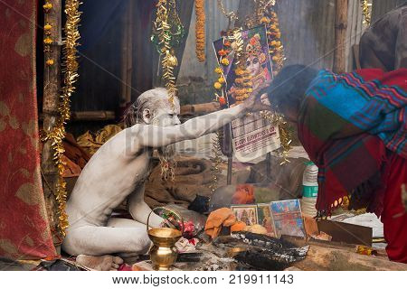 BABUGHAT KOLKATA WEST BENGAL / INDIA - 11TH JANUARY 2015 : Hindu Sadhu with white ash applied on body and face blessing blue sari clad Indian devotee woman.