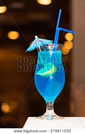 Cocktail with an umbrella and tubules on dark background
