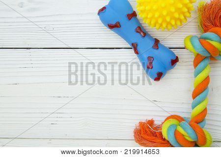 Pet care, veterinary, grooming concept. Pets having fun. A white wooden background with dog toys-a yellow rubber ball, a blue rubber bone and a colorful rope bone. Space for your text or image.