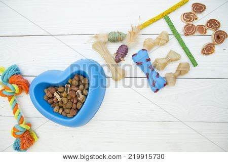 Pet care, veterinary, grooming concept. Nutritious food for your buddy. I love pets inscription made of dog toys, snacks and a bowl of dry dog food on a white wooden background.
