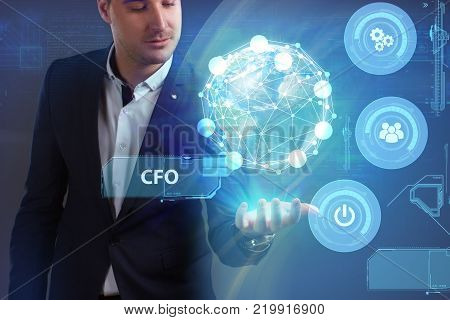 Business Technology Internet and network concept. Young businessman working on a virtual screen of the future and sees the inscription: CFO